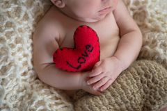 拿着一个心形的枕头的婴孩 库存图片