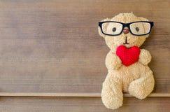 拿着一个心形的枕头的玩具熊 图库摄影