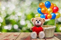 拿着一个心形的枕头的玩具熊 免版税库存图片