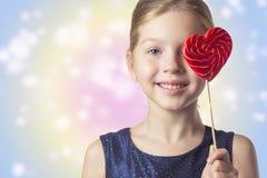 拿着一个心形的棒棒糖的女孩孩子 tonin的作用 免版税库存图片