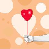 拿着一个心形的气球的手 免版税库存照片