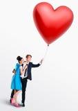 拿着一个心形的气球的男人和妇女 库存图片