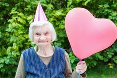 拿着一个心形的气球的年长夫人 免版税图库摄影