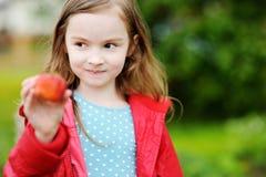 拿着一个成熟草莓的逗人喜爱的小女孩 免版税库存图片