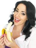 拿着一个成熟香蕉的年轻健康可爱的妇女 免版税图库摄影