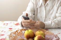 拿着一个手机的一个老妇人的手 免版税库存照片