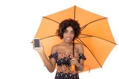 拿着一个手机的微笑的女孩在伞下 免版税库存照片