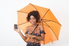 拿着一个手机的微笑的女孩在伞下 免版税库存图片