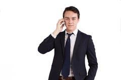 拿着一个手机的愉快的年轻白种人商人 库存照片