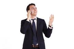 拿着一个手机的愉快的年轻白种人商人 库存图片