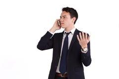 拿着一个手机的皱眉的年轻白种人商人 免版税库存照片