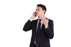 拿着一个手机的皱眉的年轻白种人商人 免版税库存图片