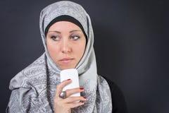 拿着一个手机的hijab的回教妇女 免版税库存照片