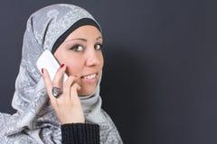 拿着一个手机的hijab的回教妇女 免版税库存图片