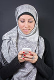 拿着一个手机的hijab的回教妇女 库存图片