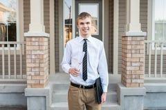 拿着一个文凭和毕业盖帽在房子前面的年轻男生 库存照片