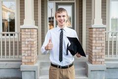 拿着一个文凭和毕业盖帽在房子前面的年轻男生 免版税库存照片