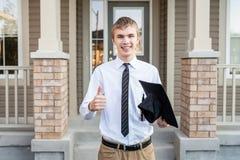 拿着一个文凭和毕业盖帽在房子前面的年轻男生 库存图片