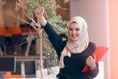 拿着一个文件夹的阿拉伯女商人在现代起始的办公室 库存照片