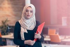 拿着一个文件夹的阿拉伯女商人在现代起始的办公室 图库摄影