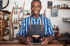 拿着一个新鲜的杯子热奶咖啡的微笑的咖啡馆barista 免版税库存图片