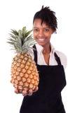 拿着一个新鲜的瓜的年轻愉快的黑人/非裔美国人的妇女 库存图片