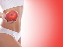 拿着一个新鲜的苹果的一个少妇的性感的身体 免版税库存图片