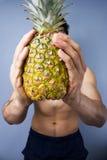 拿着一个新鲜的菠萝的运动年轻人 库存图片