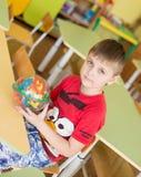 拿着一个明亮的五颜六色的球迷宫玩具在幼儿园-莫斯科,俄罗斯- 2016年2月4日的快乐的微笑的男孩画象  库存图片