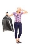 拿着一个有臭味的垃圾袋的妇女 库存图片