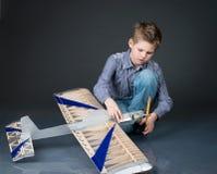 拿着一个木平面模型的青春期前的男孩 使用与真正的孩子 图库摄影