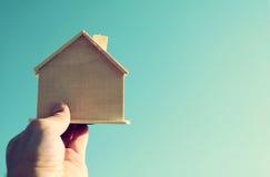 拿着一个木玩具房子的人的手反对蓝天 免版税库存图片