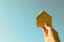 拿着一个木玩具房子的人的手反对蓝天 库存照片