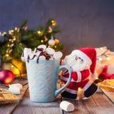 拿着一个杯子可可粉的装饰圣诞老人用在欢乐黑暗的背景的蛋白软糖与圣诞树、光和de 库存图片