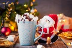 拿着一个杯子可可粉的装饰圣诞老人用在欢乐黑暗的背景的蛋白软糖与圣诞树、光和de 库存照片