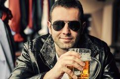 拿着一个杯子啤酒的欢悦年轻人 库存图片