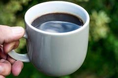拿着一个杯子无奶咖啡的人 免版税库存图片