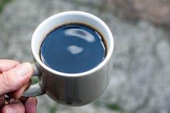 拿着一个杯子无奶咖啡的人 免版税库存照片