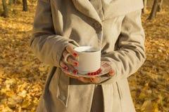 拿着一个杯子无奶咖啡的女性在森林 免版税库存图片