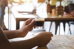 拿着一个杯子浓咖啡室外 免版税图库摄影