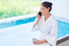 拿着一个杯子热的咖啡的白色浴巾的愉快的年轻亚裔妇女喝,当坐在使用她的电话时的游泳场附近 免版税图库摄影