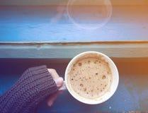 拿着一个杯子热的热奶咖啡的手 免版税库存照片