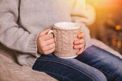 拿着一个杯子热的茶的儿童的手近 免版税图库摄影