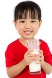 拿着一个杯子牛奶的亚裔矮小的中国女孩 库存图片