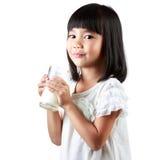 拿着一个杯子牛奶的愉快的矮小的亚裔女孩 免版税库存图片