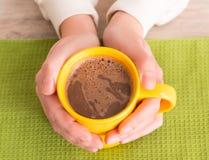 拿着一个杯子用咖啡的手 免版税库存图片