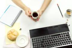 拿着一个杯子用在工作区的咖啡的女孩 库存照片
