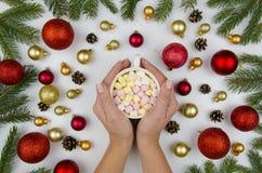 拿着一个杯子用蛋白软糖的女性手 圣诞节构成由金子和红色球做成圣诞树的,和 免版税库存照片