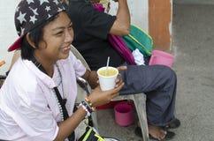 拿着一个杯子稀饭的轮椅女性叫化子 库存图片