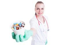 拿着一个杯子药片和胶囊的可爱的医生 免版税库存照片